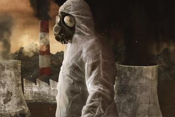 Mann mit Gasmaske und Schutzanzug vor Verbrennungsanlagen und Kraftwerke