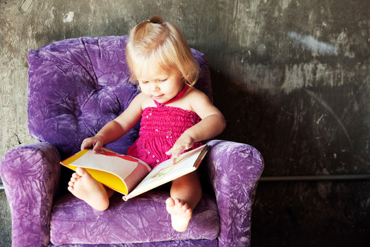 Baby reading book on purple chair (18-23 months)