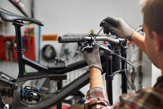 Cropped shot of male mechanic working in bicycle repair shop, serviceman repairing modern bike using special tool, wearing protective gloves