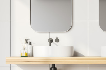 Close up white tile bathroom with sink