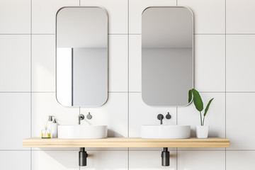Close up of white tile bathroom with double sink