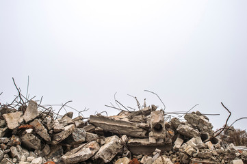 Obraz The rebar sticking up from piles of brick rubble, stone and concrete rubble against the sky in a haze. - fototapety do salonu