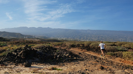 Young Caucasian male running through the badlands of Abades, between the village of Abades and Poris de Abona, on a rough pathway heading inland. Active man jogging through the wild nature in Tenerife