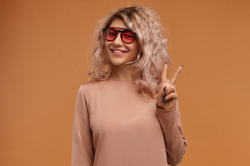 Style, fashion trends and youth concept. Picture of fashionable hipster girl wearing trendy sunglasses with pink lenses looking at camera with joyful broad smile, making peace sign, saying Hi