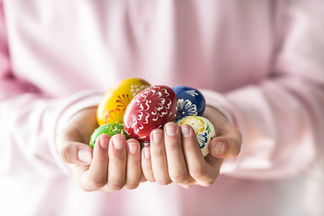 Close-up multicolored easter eggs in the girls hands