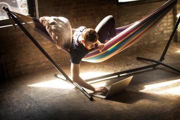 Young man surfing net in hammock
