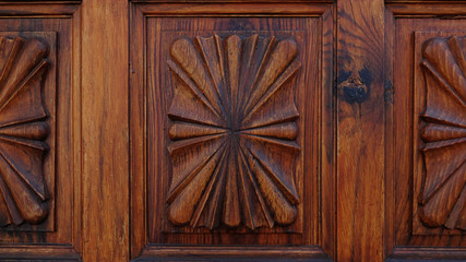 Close-up shot of a carved wooden door with classic stylized motifs forming symmetrical patterns. Ornamental background concept for home ownership, status, privacy or interior design with copy space.