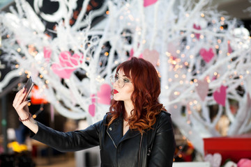 Stylish lady making selfie in the mall. Girl is photographed near the Valentine's Day scenery
