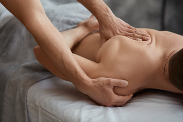 Young handsome man enjoying a back massage. Professional massage therapist is treating a male...