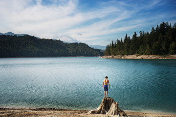 Teenage boy standing on tree stump on lake beach