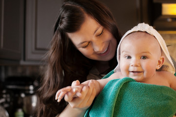 Smiling mother with little son (2-5 months) wrapped in towel