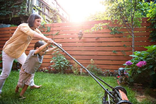 Boy (4-5) with mother mowing lawn