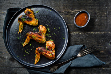 Chicken wings BBQ on the black plate. Black wooden background, side view