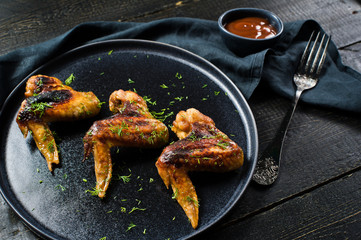 Chicken wings grilled in honey marinade on a black plate. Black wooden background, side view