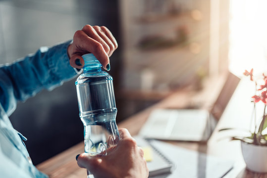 Woman opening bottle of water in the office