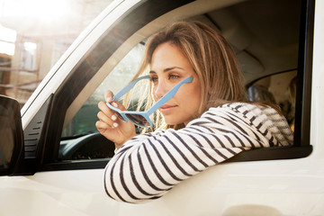Young woman sitting in car and trying on sunglasses