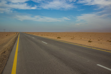 picturesque scenery desert landscape with yellow sand wilderness environment and asphalt empty highway car road, infrastructure and transportation concept photography, copy space