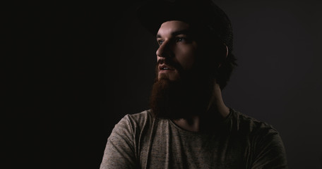 Handsome bearded man in tshirt and hat with crossed arms looking away on darkling background