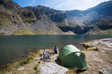 Mountain biker camping on lakeshore