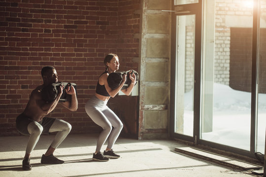 Young mixed-race fit couple doing squats exercise, while holding in hands heavy sandbag during group circuit functional training at the well-lit gym with panoramic windows.