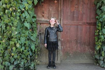 Beautiful blond little girl, dressed in rock and roll style: black leather jacket, skirt and boots sunglasses. The girl stays in front of old wooden gate, a green ivy.