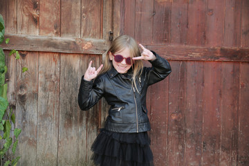Beautiful blond little girl, dressed in rock and roll style: black leather jacket, skirt and boots sunglasses. The girl stays in front of old wooden gate, a green ivy and making a rock-n-roll sign.