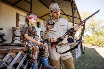 Man teaching girl (6-7) how to use gun