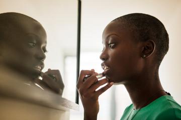 Portrait of young bald woman applying lipstick