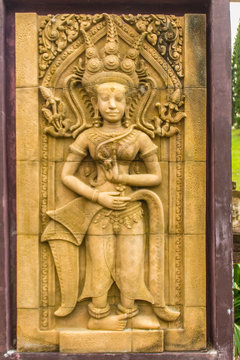 An Apsara dancing carved on the sandstone wall background. Apsara is a female spirit of the clouds and waters in Hindu culture. Her figure prominently in the sculpture, dance, literature and painting.