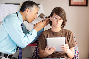 Boy (12-13) using tablet during doctor's appointment