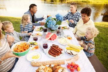 Family with children (2-3, 4-5, 6-7) sitting at dining table outdoors