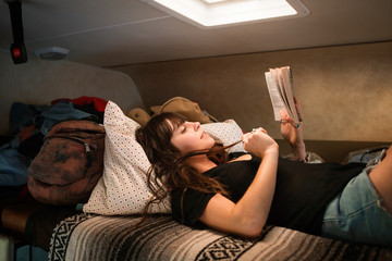 Young woman reading book at motor home