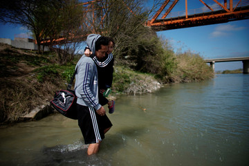 Migrant carries a child as he crosses the Rio Bravo towards the United States, in Piedras Negras