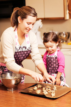 Daughter (2-3) and mother making cookies in domestic kitchen