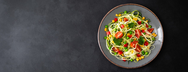 Zoodlie, healthy vegan food - zucchini noodlie with fresh green peas, tomato, bell pepper and corn for lunch, view from above