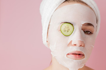 Beautiful young woman is applying a cosmetic tissue mask on a face with cucumber on a pink background