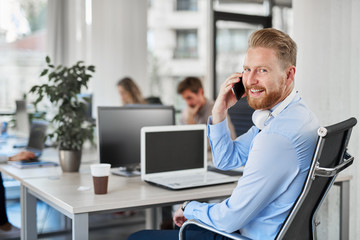 Smiling ginger CEO looking over shoulder and talking on the phone while sitting in modern office.