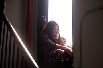 Mid-adult woman sitting on window sill with her daughter (10-11)