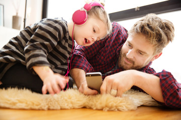 Father and daughter (4-5) lying on rug listening to music
