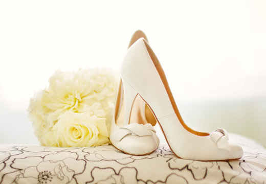 Bridal shoes with flowers on cushion