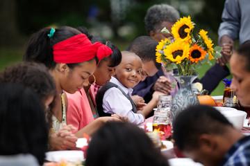 Boy smiling during family prayer at dinner