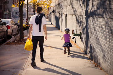Small girl (2-3) riding on bicycle with father