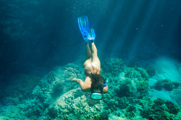 Young woman free diving above coral reef