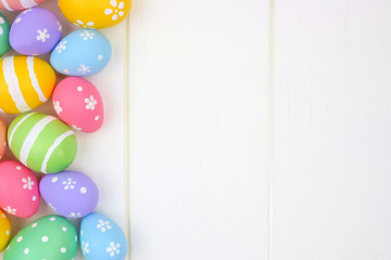 Colorful pastel Easter Egg side border against a white wood background. Top view with copy space.