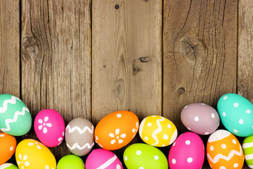 Colorful Easter Egg bottom border against a rustic wood background. Above view with copy space.