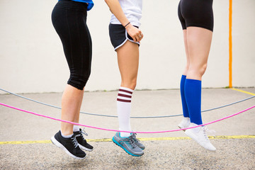 Legs of three women jumping over skipping ropes
