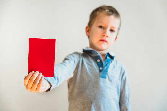 Angry face child showing a red card as a warning, stop bullying concept, blank background.