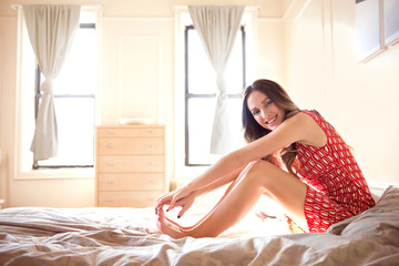 Happy woman sitting on bed