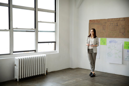 Portrait of young woman standing before makeshift charts on wall of loft apartment
