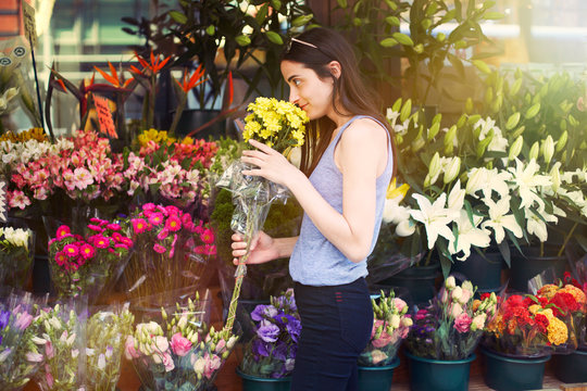 Young woman smelling flower in flower shop